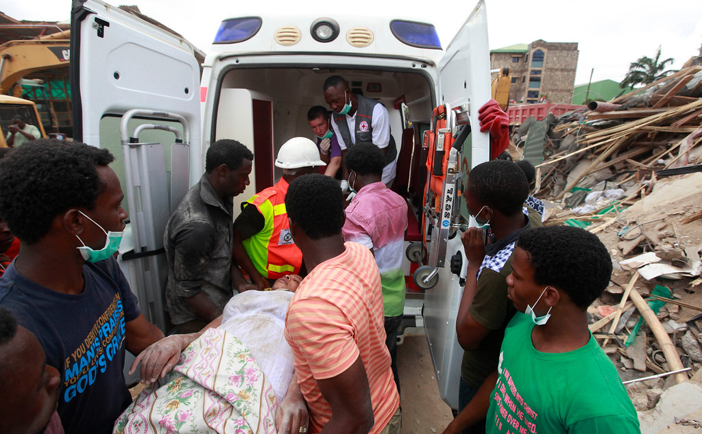 . Rescue workers carry a survivor into an ambulance, from the rubble of a collapsed building belonging to the Synagogue Church of All Nations in Lagos, Nigeria, Saturday, Sept, 13. 2014. The building was being extended, adding 2 additional floors when it collapsed. (AP Photo/Sunday Alamba)