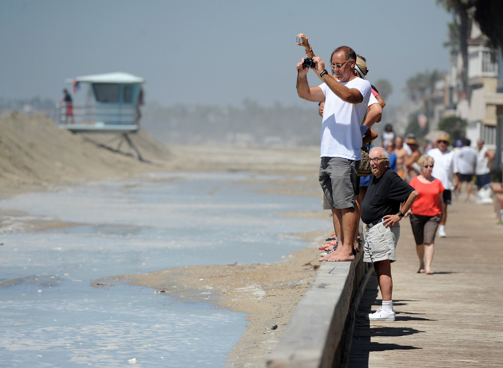 . A crowd lines Seaside Walk in the Peninsula neighborhood to watch crew shore up a sand berm in Long Beach, CA on Wednesday, August 27, 2014. With city crews constantly building a sand berm, the water was held back from the homes and streets during the morning high tide. (Photo by Scott Varley, Daily Breeze)