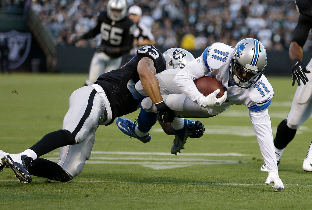. Detroit Lions wide receiver Kevin Ogletree (11) is tackled by Oakland Raiders defensive back Tyvon Branch (33) during the first quarter of an NFL preseason football game in Oakland, Calif., Friday, Aug. 15, 2014. (AP Photo/Ben Margot)
