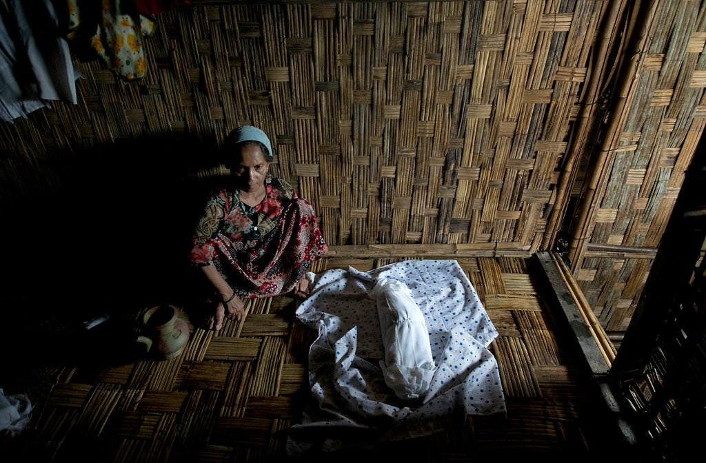 . In this June 27, 2014 photo, Hasina Begum sits next to the tiny corpse of her granddaughter, who died just four hours after she was born in squalid camp for victims of sectarian violence in north of Sittwe, Rakhine state, Myanmar. The body was washed with warm water and then wrapped in clothe. With little or no access to life-saving medical treatment, infant and maternal mortality is one of the leading causes of death in the camps, home to 140,000 Rohingya. Midwives say the situation seems to be worsening by the day. (AP Photo/Gemunu Amarasinghe)