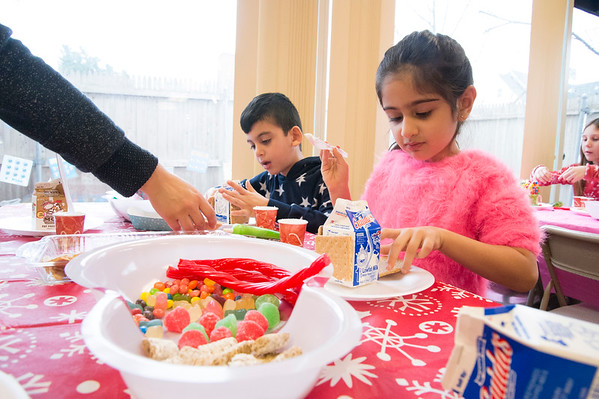 12/27/19 Wesley Bunnell | StaffrrGingerbread house making took place on Friday afternoon at the New Britain Youth Museum in New Britain. Fahad Akberzai, age 7, and his sister Hira, age 5, work on their houses with an assist in breaking the ginger bread from mom.