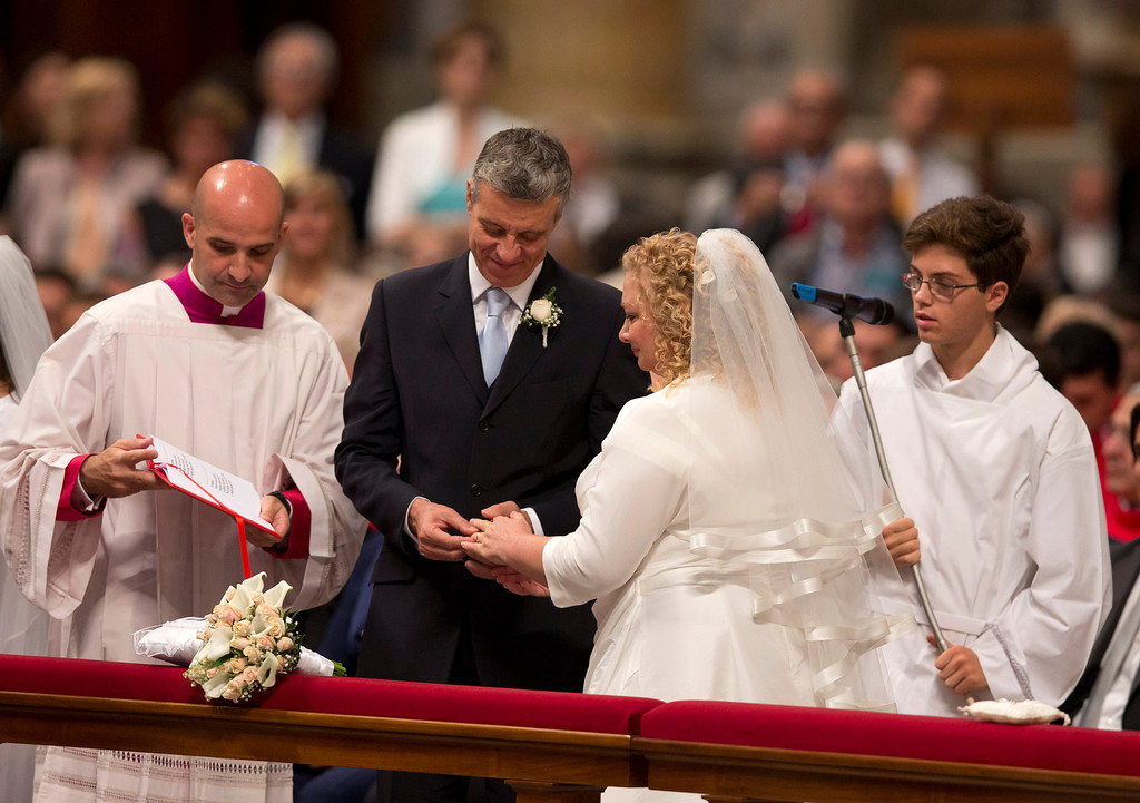 . Guido Tassara, left, and Gabriella Improta, just married by Pope Francis,  exchange rings during a wedding ceremony  in St. Peter\'s Basilica at the Vatican, Sunday, Sept. 14, 2014. (AP Photo/Alessandra Tarantino)