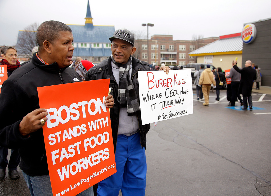 """. Pedro Rodriguez, right, talks with Andrus Reyes as they participate in a demonstration on a Burger King parking lot as part of a nationwide protest supporting higher wages for workers in the fast-food industry and other minimum wage jobs in Boston, Thursday, Dec. 5, 2013. Rodriguez was once an employee of this Burger King restaurant before being \""""let go\"""" and Reyes  works for Local 32 VJ, the union who represents workers hired to clean the restaurant they are protesting. (AP Photo/Stephan Savoia)"""