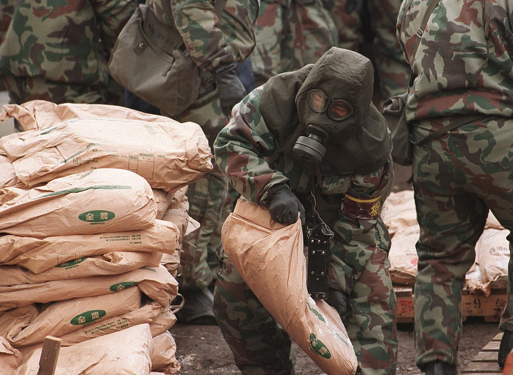Description of . A policeman wearing a gas mask and an anti-chemical suit carries a sack of chemicals from the main commune of the doomsday cult Aum Supreme Truth at Kamikuishiki village, 100 km west of Tokyo, on March 23, 2000. A total of 1,100 policemen including an anti-riot unit, resumed their raid, seizing two tons of chloroform and ethanol, as well as more than 15 cans of ethyl ether, about 10 bottles of unidentified yellow-colored liquid and gas.  YOSHIKATSU TSUNO/AFP/Getty Images