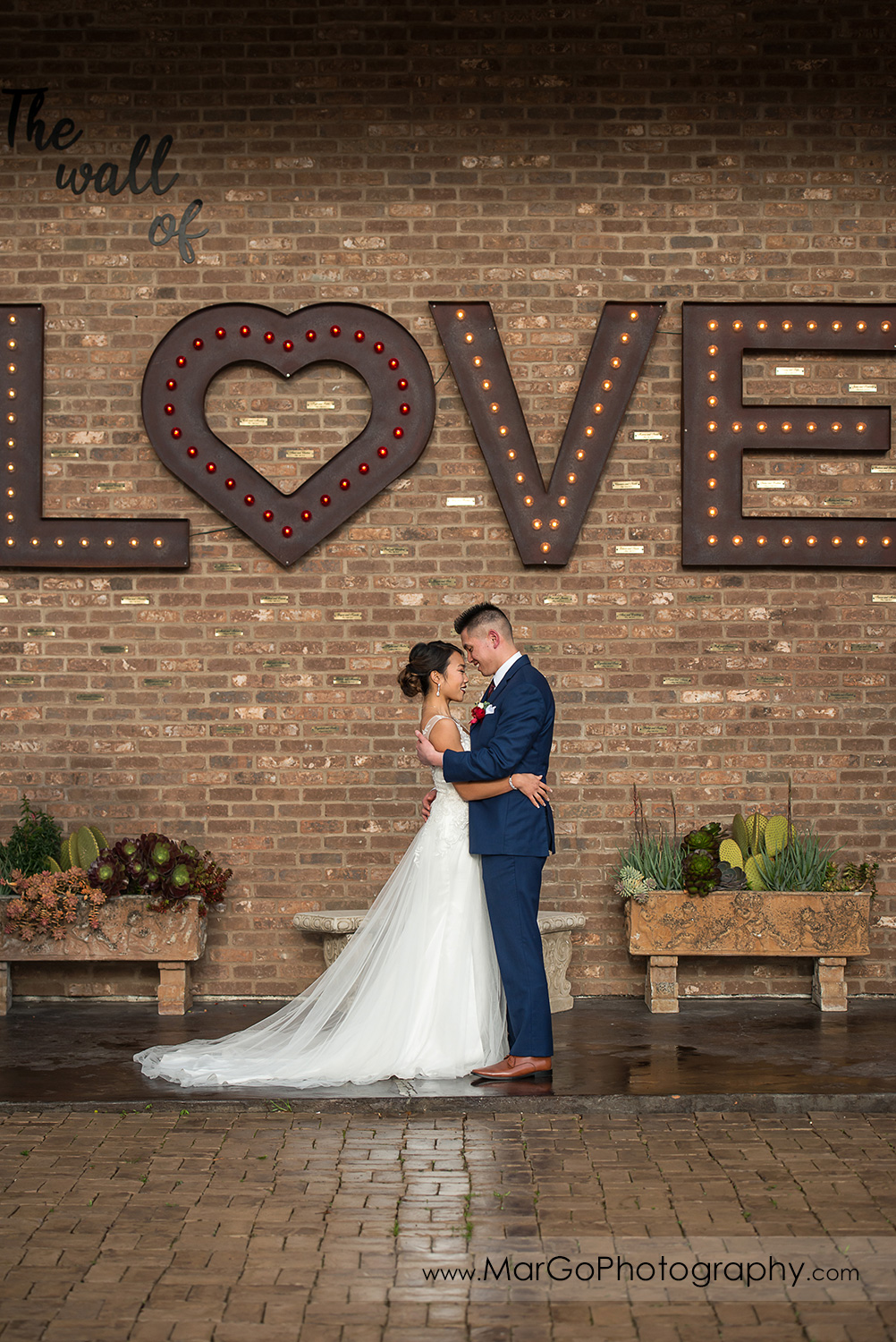 bride and groom under LOVE sign at Sunol's Casa Bella