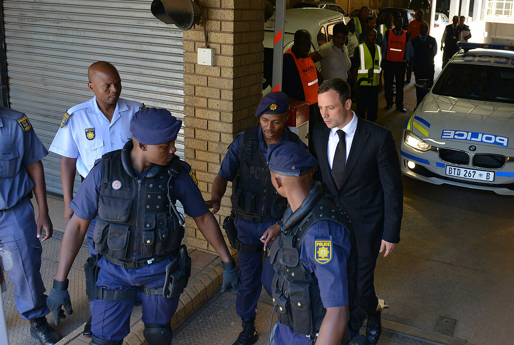 . Oscar Pistorius, rear right, is led to a awaiting police vehicle to be taken to prison outside the court in Pretoria, South Africa, Tuesday, Oct. 21, 2014.  (AP Photo/Antoine de Ras, Independent Newspapers)