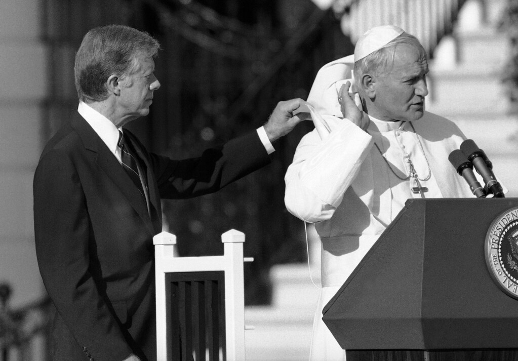 . U.S. President Jimmy Carter gives Pope John Paul II a hand with his cape, blown up by a breeze during ceremonies on the South Lawn of the White House in Washington, Saturday, Oct. 6, 1979. (AP Photo)