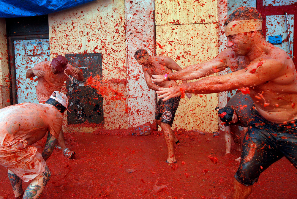 ". Men throw tomatoes at each other, during the annual ""tomatina\"" tomato fight fiesta in the village of Bunol, 50 kilometers outside Valencia, Spain, Wednesday, Aug. 27, 2014. The streets of an eastern Spanish town are awash with red pulp as thousands of people pelt each other with tomatoes in the annual \""Tomatina\"" battle that has become a major tourist attraction. At the annual fiesta in Bunol on Wednesday, trucks dumped 125 tons of ripe tomatoes for some 22,000 participants, many from abroad to throw during the hour-long morning festivities. (AP Photo/Alberto Saiz)"