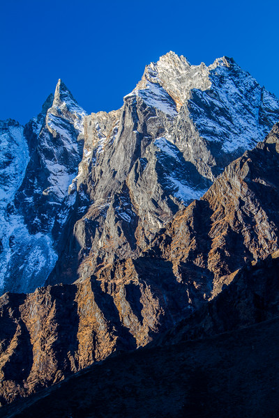 Rather sharp jagged peaks jut up from the Himalayas of Nepal against a pure blue sky