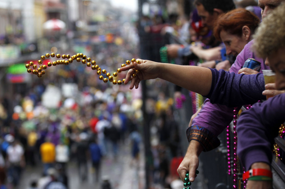 . People throw beads from the balcony of the Royal Sonesta Hotel to crowds below on Bourbon Street during Mardi Gras in New Orleans, Tuesday, Feb. 12, 2013.  Despite threatening skies, the Mardi Gras party carried on as thousands of costumed revelers cheered glitzy floats with make-believe monarchs in an all-out bash before Lent.   Crowds were a little smaller than recent years, perhaps influenced by the forecast of rain. Still, parades went off as scheduled even as a fog settled over the riverfront and downtown areas. (AP Photo/Gerald Herbert)