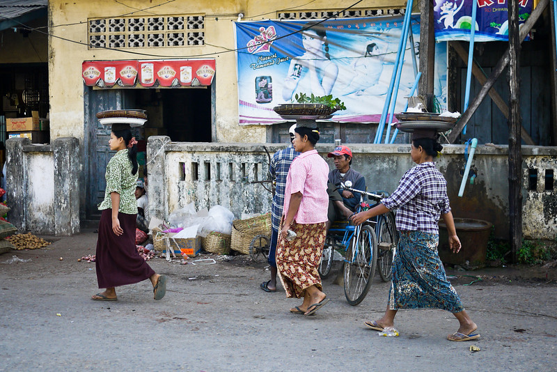 Women balance their wares on their heads as they walk through the streets of Hpa-An, Burma.