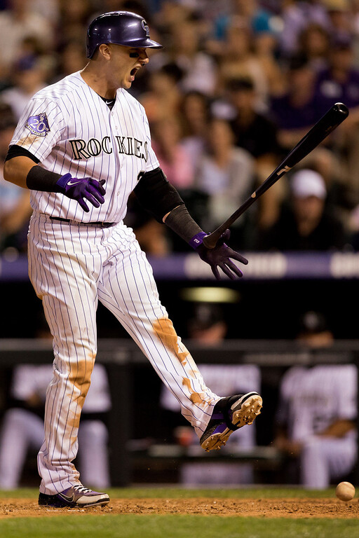 . DENVER, CO - JULY 19:  Troy Tulowitzki #2 of the Colorado Rockies reacts after striking out in the seventh inning against the Chicago Cubs picks up the ball at Coors Field on July 19, 2013 in Denver, Colorado.  (Photo by Justin Edmonds/Getty Images)
