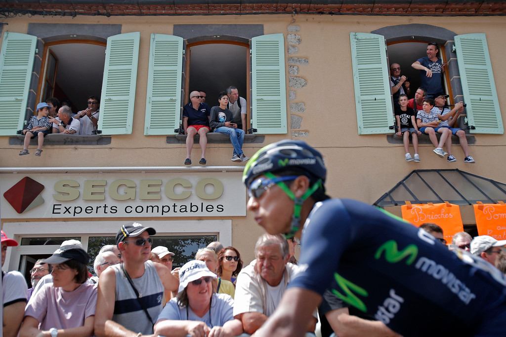 . Spectators watch from windows as Nairo Alexander Quintana of Colombia arrives prior to the fourteenth stage of the Tour de France cycling race over 191 kilometers (119.4 miles) with start in in Saint-Pourcain-sur-Sioule and finish in Lyon, central France, Saturday July 13 2013. (AP Photo/Christophe Ena)
