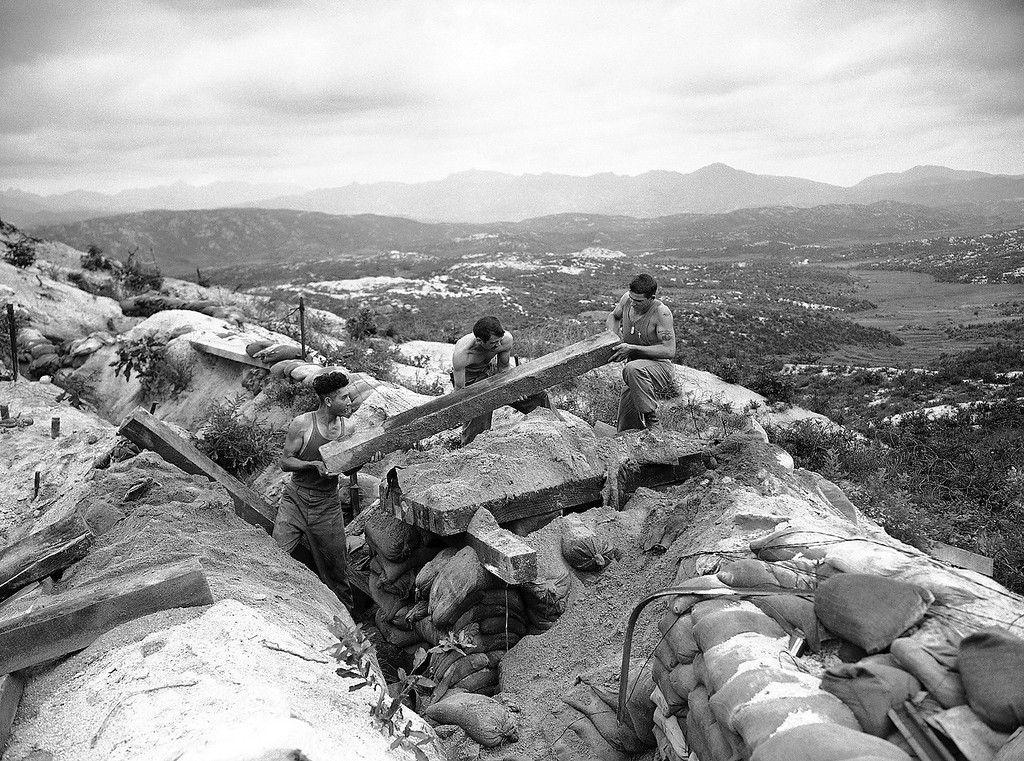 . Three American Marines, left to right are: Pfc. Clarence Hara, Alumbank, Pa.; Cpl. Jean Holland, Americus, Ga.; and Pfc. Carl Toker, Mt. Wolf, Pa., destroy their bunkers on a forward observation post on the western front preparatory to withdrawal from the demilitarized zone under terms of the armistice in Korea July 28, 1953. In background is what was once no-man\'s land. (AP Photo/CLH)