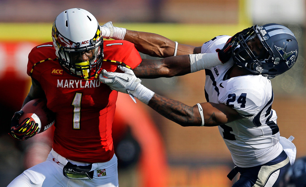 . Maryland wide receiver Stefon Diggs, left, pushes past Old Dominion safety Fellonte Misher while running for a touchdown in the first half of an NCAA college football game in College Park, Md., Saturday, Sept. 7, 2013. (AP Photo/Patrick Semansky)