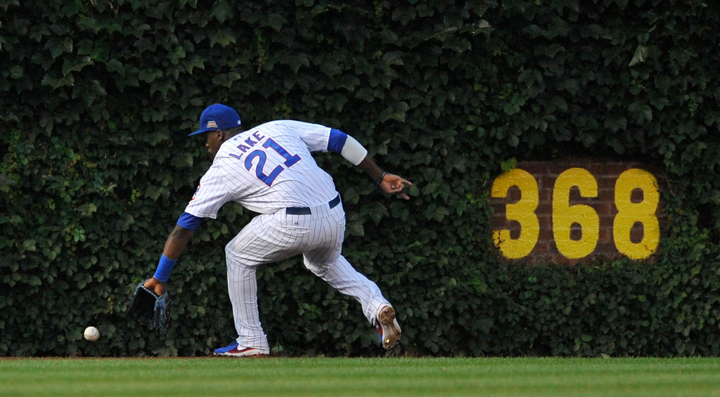 . Chicago Cubs center fielder Junior Lake misses a RBI double hit by Colorado Rockies\' Charlie Blackmon during the second inning of a baseball game in Chicago, Wednesday, July 30, 2014. (AP Photo/Paul Beaty)