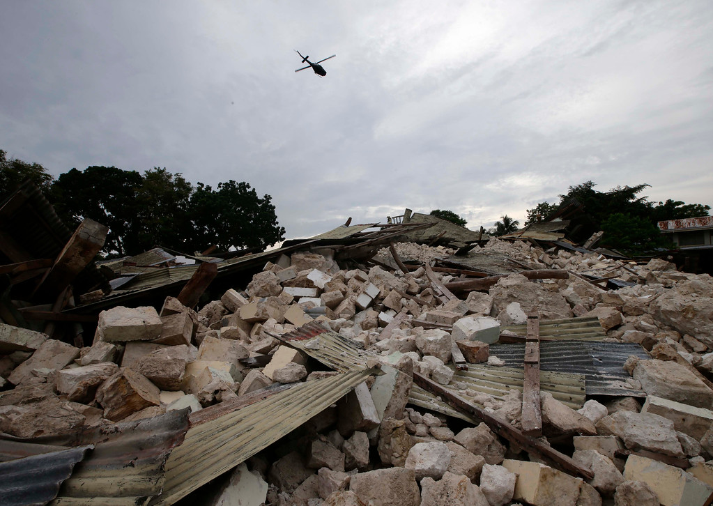 . A Philippine Air Force helicopter hovers above the totally-collapsed Our Lady of Light church at Loon township, Bohol province in central Philippines Thursday Oct.17, 2013.  (AP Photo/Bullit Marquez)