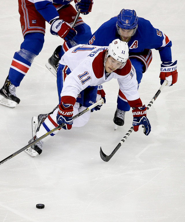 . Montreal Canadiens right wing Brendan Gallagher (11) tries to seal off New York Rangers defenseman Dan Girardi (5) from the puck during the second period in Game 6 of the NHL hockey Stanley Cup playoffs Eastern Conference finals, Thursday, May 29, 2014, in New York. (AP Photo/Frank Franklin II)