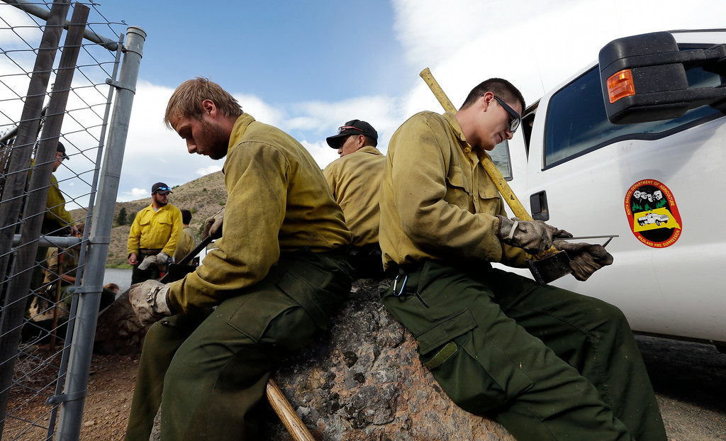 . Firefighters Alex Keller, left, and Jacey Mesteth sharpen their tools as they wait to be deployed to a fire line Saturday, July 19, 2014, in Winthrop, Wash. A wind-driven, lightning-caused wildfire racing through rural north-central Washington destroyed about 100 homes Thursday and Friday, leaving behind solitary brick chimneys and burned-out automobiles as it blackened hundreds of square miles in the scenic Methow Valley northeast of Seattle. (AP Photo/Elaine Thompson)