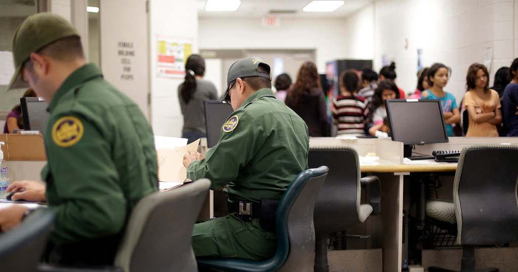 . U.S. Customs and Border Protection agents work at a processing facility, Wednesday, June 18, 2014, in Brownsville,Texas.   (AP Photo/Eric Gay, Pool)
