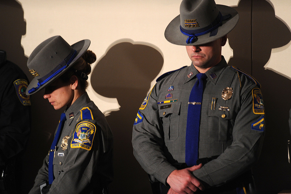 . Members of the Connecticut state police bow their heads during a memorial service for victims of the Sandy Hook Elementary School shooting at Newtown High School in Newtown, Connecticut, U.S., on Sunday, Dec. 16, 2012. Obama arrived in Newtown, Connecticut, two days after the tragedy and as authorities were still trying to piece together a motive for the second-deadliest mass shooting in the U.S. Photographer: Olivier Douliery/Pool via Bloomberg