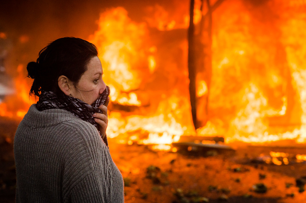 . A woman uses a scarf to protect herself against teargas as she stands in front of a burning car, during a national trade union demonstration in Brussels, Thursday Nov. 6, 2014.  (AP Photo/Geert Vanden Wijngaert)