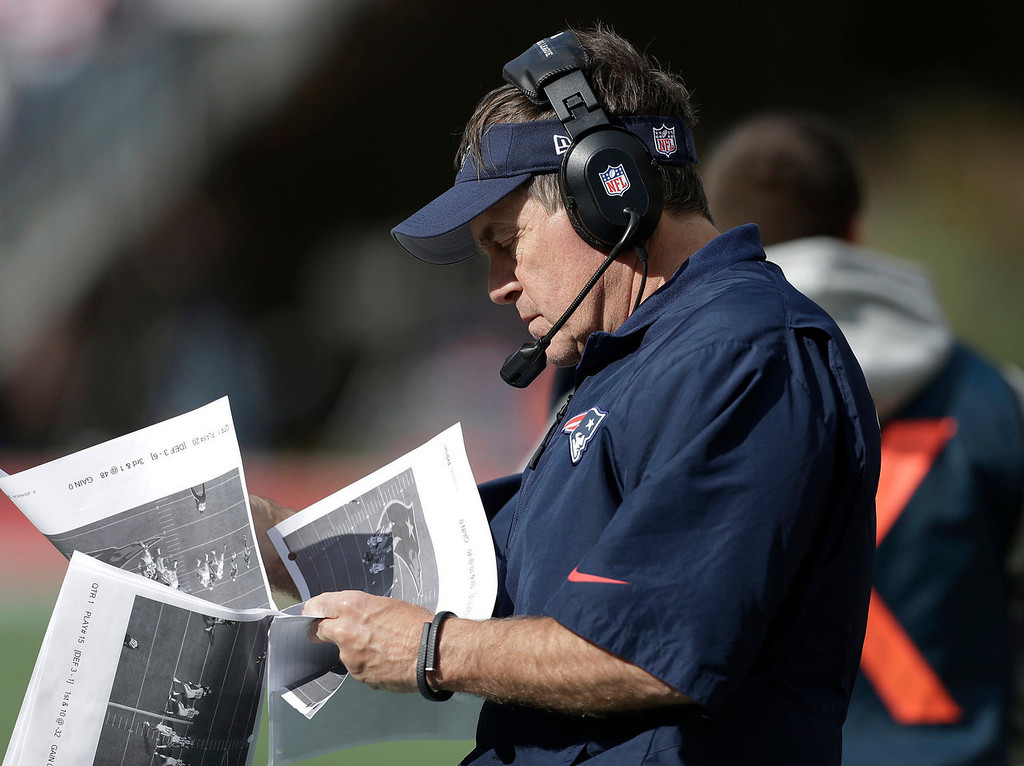 . New England Patriots head coach Bill Belichick studies pictures on the sideline in the second quarter of an NFL football game against the Miami Dolphins Sunday, Oct. 27, 2013, in Foxborough, Mass. (AP Photo/Steven Senne)
