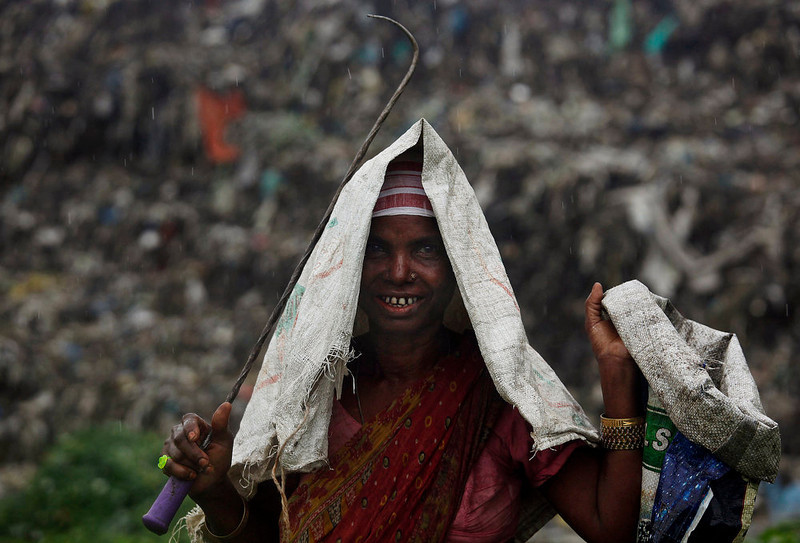 . Zahira Biwi, an Indian ragpicker smiles as she works in a garbage dump near Deepor Beel wildlife sanctuary on the outskirts of Gauhati, India, Wednesday, June 5, 2013. The World Environment Day is celebrated June 5 every year by the United Nations to stimulate global awareness on environmental issues. (AP Photo/Anupam Nath)