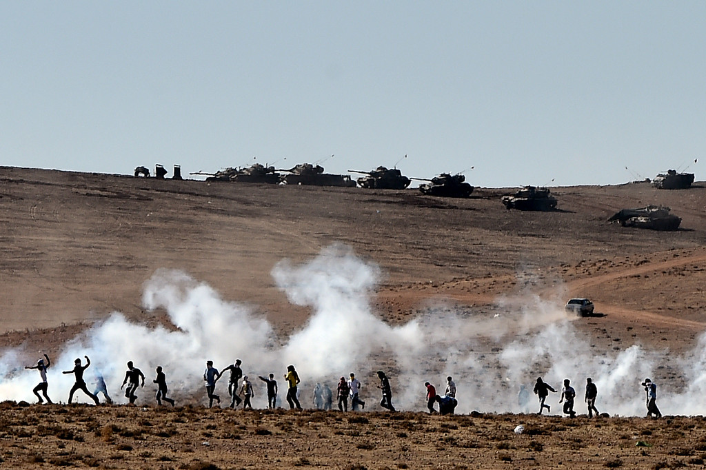 . Kurdish people throw stones at Turkish armoured vehicles firing tear gas as Turkish army soldiers try to remove people from the Turkish-Syrian border area near the Syrian town of Ain al-Arab, known as Kobane by the Kurds, in the southeastern town of Suruc, Sanliurfa province, on October 7, 2014. ARIS MESSINIS/AFP/Getty Images