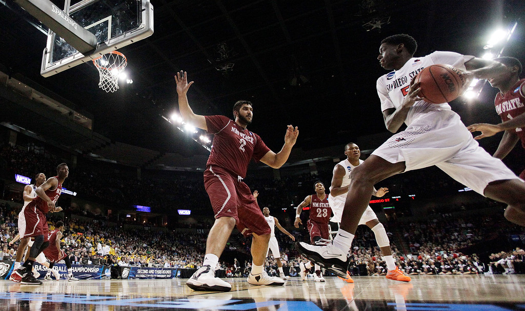 . San Diego State�s Dwayne Polee II, right, drives to the basket against New Mexico State�s Sim Bhullar (2) during the first half of a second-round game of the NCAA men\'s college basketball tournament in Spokane, Wash., Thursday, March 20, 2014. (AP Photo/Young Kwak)