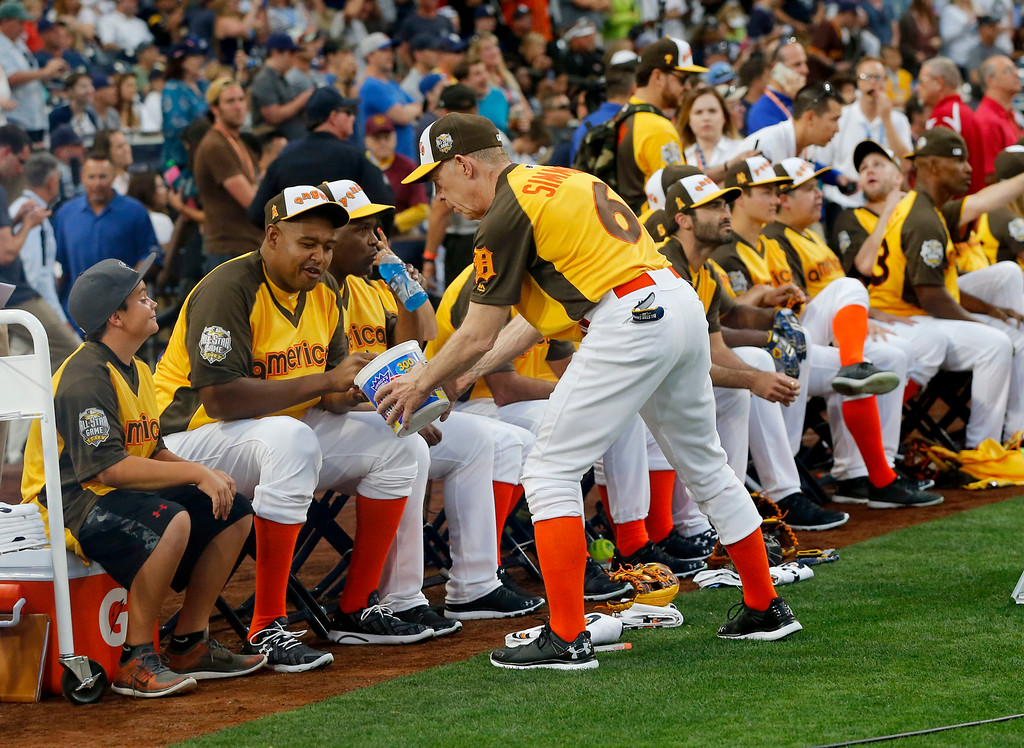 . Actor J.K. Simons passes out gum to his teammates during the All-Star Legends & Celebrity Softball game, Sunday, July 10, 2016, in San Diego. (AP Photo/Lenny Ignelzi)