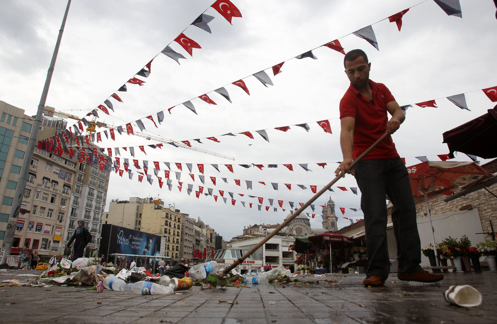 . A flower vendor clears an area in front of his shop as Turkish and European Union flags hang over him at the Taskim square in Istanbul, Sunday, June 2, 2013. Protests in Istanbul and several other Turkish cities appear to have subsided, after days of fierce clashes following a police crackdown on a peaceful gathering as protesters denounced what they see as Prime Minister Recep Tayyip Erdogan\'s increasingly authoritarian style. (AP Photo/Thanassis Stavrakis)