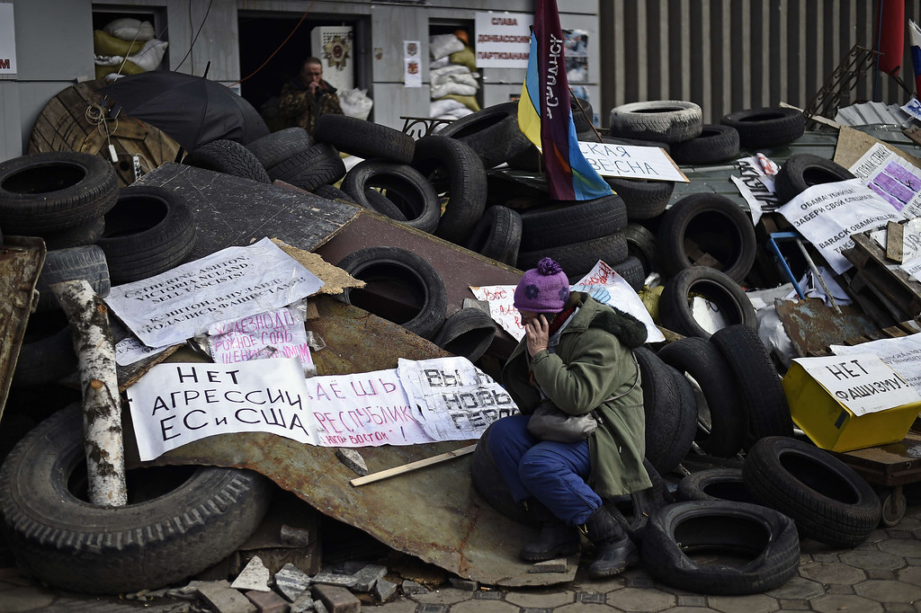 . A Pro-Russia activist sits on a barricade outside the secret service building in the eastern Ukrainian city of Lugansk on April 14, 2014.   AFP PHOTO / DIMITAR  DILKOFF/AFP/Getty Images