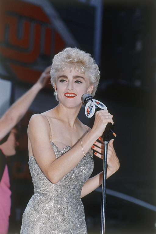 """. Madonna greets her fans from a platform in Times Square, near the Broadway movie theater, where her new film, \""""Who\'s That Girl\"""" made its New York debut, Aug. 6, 1987.  (AP Photo)"""