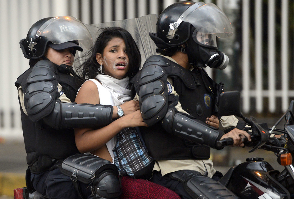 ". An anti-government activist is arrested by national police during a protest against Venezuela President Nicolas Maduro government in Caracas on March 13, 2014. A total of 28 people have been killed and 365 injured in anti-government protests rocking Venezuela, the country\'s top prosecutor said Thursday, lamenting an atmosphere of ""violence and chaos\"".AFP PHOTO/LEO RAMIREZ/AFP/Getty Images"