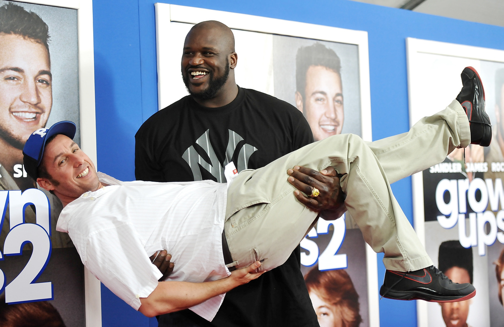 ". Former professional basketball player Shaquille O\'Neal gives actor Adam Sandler a lift at the premiere of ""Grown Ups 2\"" at the AMC Loews Lincoln Square on Wednesday, July 10, 2013 in New York. (Photo by Evan Agostini/Invision/AP)"