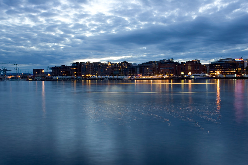 Moody, atmospheric image of downtown Oslo reflected on the harbor water. Long exposure.