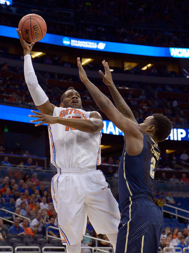 . Florida forward Will Yeguete (15) aims for the basket over Pittsburgh forward Michael Young (2), during the first half in a third-round game in the NCAA college basketball tournament, Saturday, March 22, 2014, in Orlando, Fla. (AP Photo/Phelan M. Ebenhack)