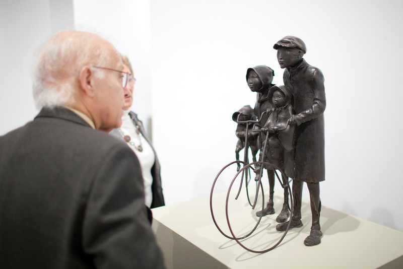 Senior man looking at a bronze sculpture by the Dutch artist Cornelis Zitman (born in 1926), exhibited in Santa Ines gallery, Seville, Andalusia, Spain