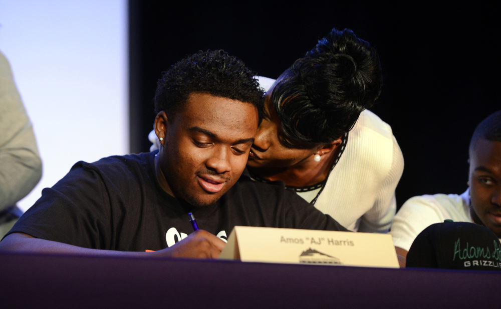 """. South High School football player Amos \""""AJ\"""" Harris gets a kiss from his mother, Tina, during a signing day ceremony in Denver, CO February  06, 2013. Harris signed with Adams State University. (Photo By Craig F. Walker/The Denver Post)"""