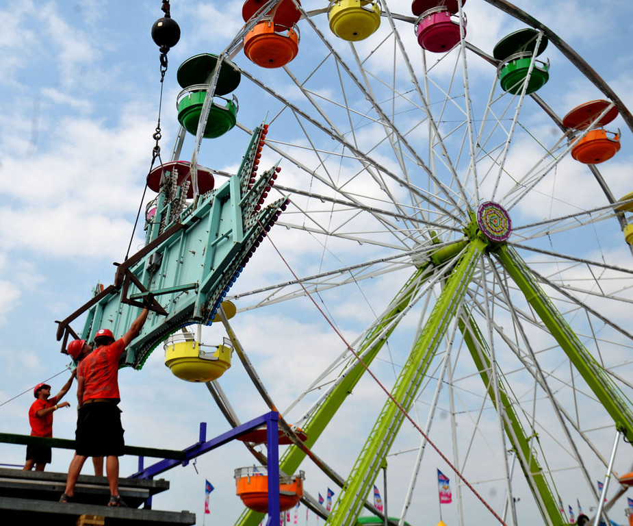 . Workmen guide in a crane-lifted sign for the \'Galaxy Ride\' in the Midway at the Minnesota State Fair on Monday, August 19, 2013 as work crews get for opening day. (Pioneer Press: John Doman)