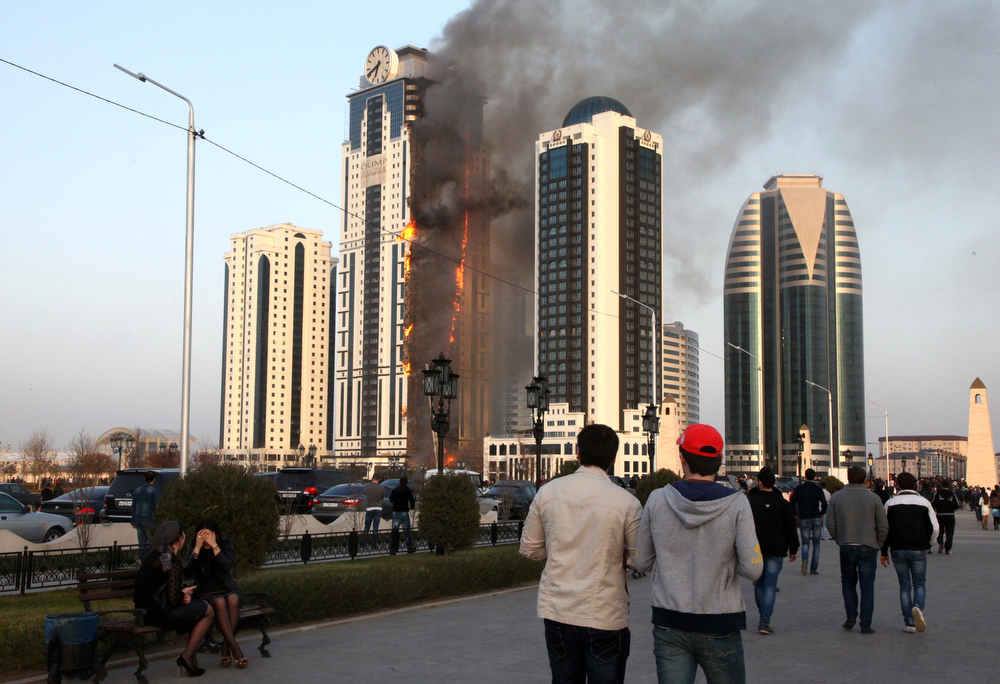 . Chechen people look at burning skyscraper in central Grozny on April 3, 2013. A fire raged in a skyscraper in the Chechnya capital Grozny on Wednesday, a building which is a centrepiece of a drive by local authorities to promote the city as a glitzy and modern hub. The buildng is uninhabited.  ELENA FITKULINA/AFP/Getty Images