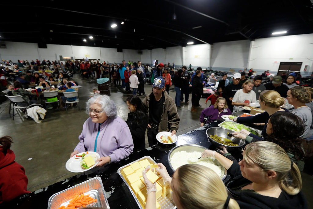 . Evacuees from city\'s surrounding the Oroville Dam line up for dinner at a shelter Monday, Feb. 13, 2017, in Chico, Calif. The thousands of people who were ordered to leave their homes after a damaged California spillway threatened to unleash a 30-foot wall of water may not be able to return until significant erosion is repaired, authorities said Monday. (AP Photo/Marcio Jose Sanchez)
