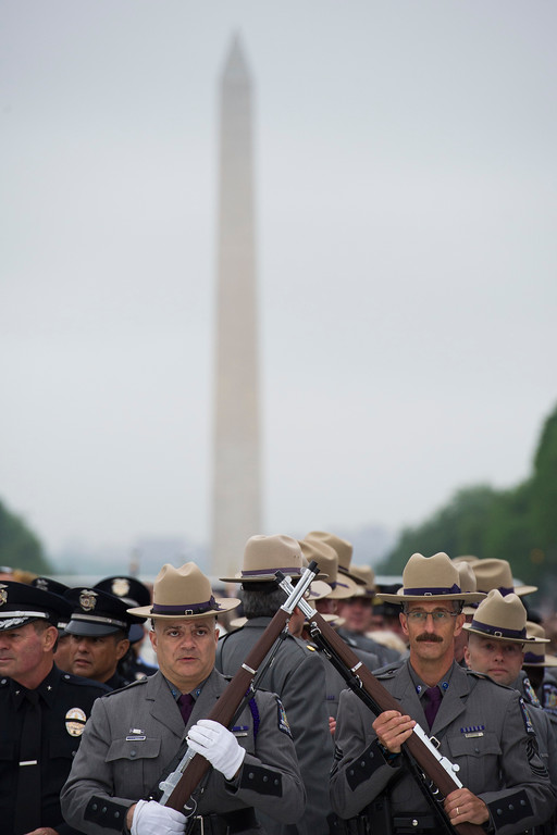 . With the Washington Monument in the background members of the New York State Police Honor Guard stand at attention during the National Law Enforcement Officers Memorial Fund 30th annual Candlelight Vigil, to commemorate new names added to the monument, on the Mall in Washington, Sunday, May 13, 2018. (AP Photo/Cliff Owen)