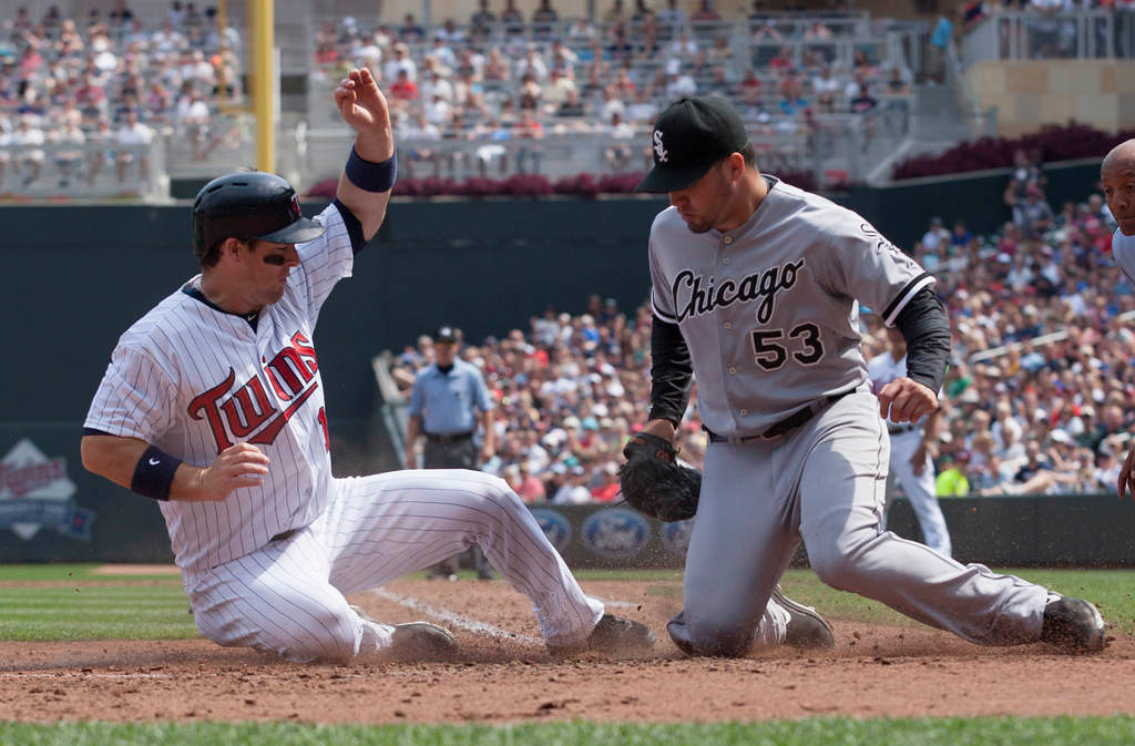. Minnesota Twins\' Josh Willingham, left, is tagged out by Chicago White Sox starting pitcher Hector Santiago after trying to score from third on a passed ball during the fourth inning of a baseball game on Sunday, Aug. 18, 2013, in Minneapolis. (AP Photo/Paul Battaglia)