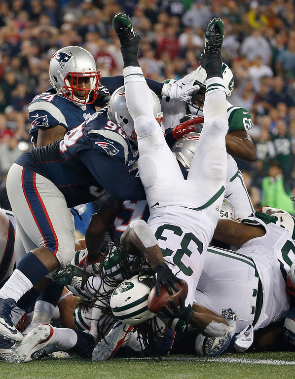 . New York Jets running back Chris Ivory (33) lands in the end zone for a touchdown in the third quarter of an NFL football game against the New England Patriots on Thursday, Oct. 16, 2014, in Foxborough, Mass. (AP Photo/Elise Amendola)