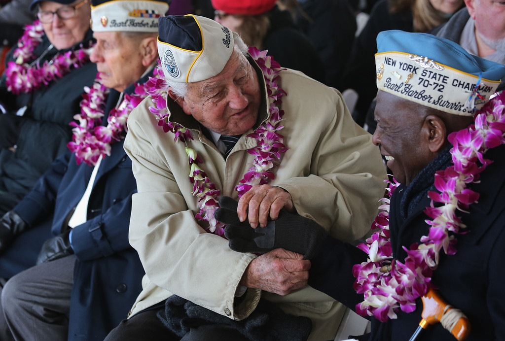 . Pearl Harbor survivor Armando Galella, 92, helps fellow survivor Clark Simmons, 92, with his gloves at a ceremony marking the 72nd anniversary of the attack on Pearl Harbor, Hawaii on December 7, 2013 in New York City. Four Pearl Harbor survivors from the New York area gathered with former crew members of the USS Intrepid to mark the Japanese surprise attack on December 7, 1941 which killed 2,402 Americans and brought the United States into WWII.  (Photo by John Moore/Getty Images)