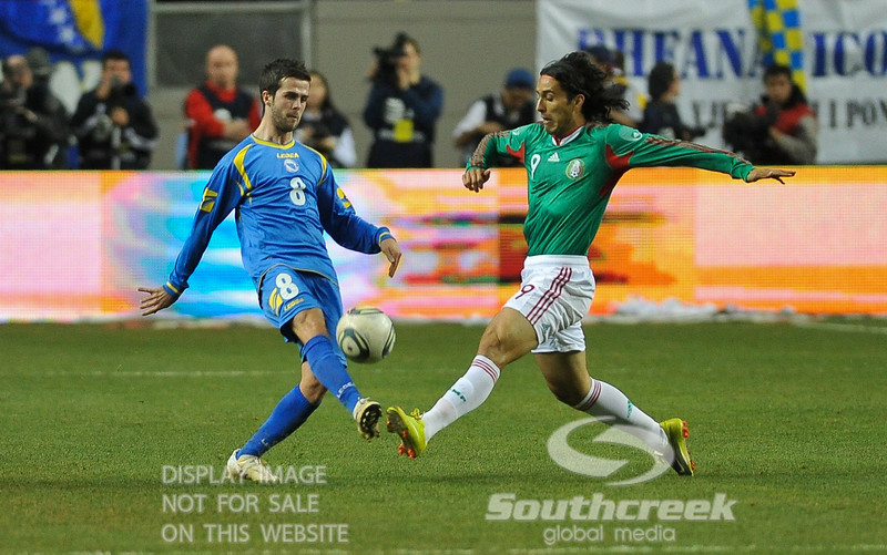 Bosnia-Herzegovina's Midfielder Miralem Pjanic (#8) and Mexico's Forward Aldo De Nigris (#9) both go after the ball in Soccer action between Bosnia-Herzegovina and Mexico.  Mexico defeated Bosnia-Herzegovina 2-0 in the game at the Georgia Dome in Atlanta, GA.