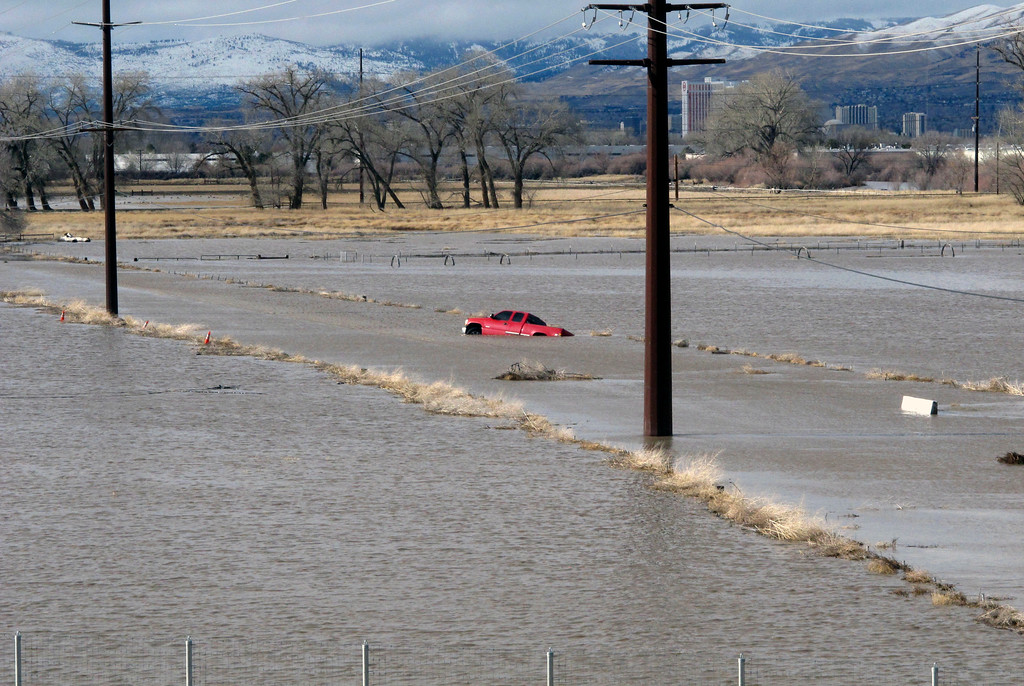 . A red pickup truck sits abandoned it after it got stuck in floodwaters Monday, Jan. 9, 2017, on a closed road at a University of Nevada, Reno, research farm bordering the Truckee River south of U.S. Interstate 80. (AP Photo/Scott Sonner).