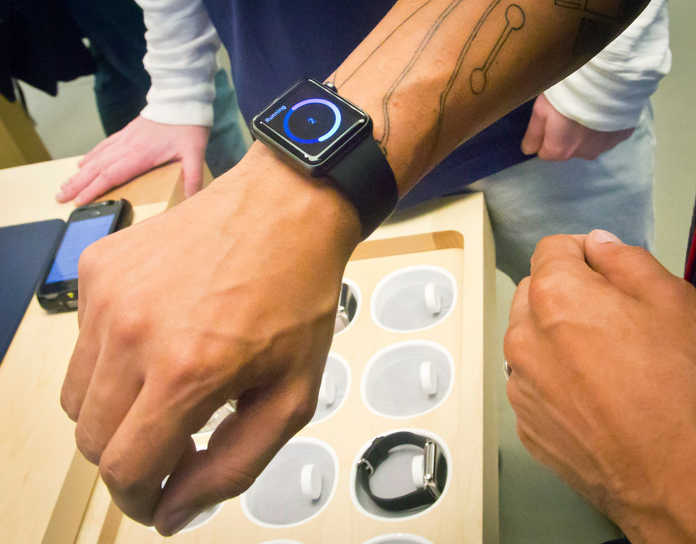 . Customers examine Apple\'s new watch which could only be bought pre-order online, Friday, April 10, 2015, in New York. Shipments are scheduled to start April 24.  (AP Photo/Bebeto Matthews)